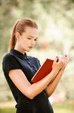 Young woman in dark blouse reads Royalty Free Stock Photos