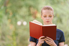 Young woman in dark blouse reads red book Stock Image