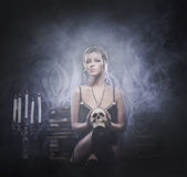 A young woman on a dark and evil background Royalty Free Stock Photography