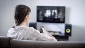 Young woman watching TV sitting on the sofa in the living room, she switches the channels using the remote control. A young woman with dark hair is in her stock video footage