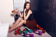 Young woman with dark hair posing in wardrobe room with lot of shoes Stock Images