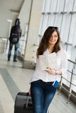 Young woman with dark hair in a white blouse goes with a suitcase holding a map at the train station. Stock Image