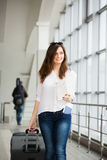 Young woman with dark hair in a white blouse goes with a suitcase holding a map at the train station. Stock Photography
