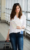 Young woman with dark hair in a white blouse goes with a suitcase holding a map at the train station. Stock Photos