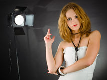 Young woman in dark studio. Backstage in studio with monolight and young woman Royalty Free Stock Images