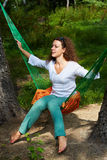 Young woman with dark sunglasses in her hair sits in hammock. On orange underlay Stock Photos