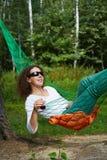 Young woman in dark sunglasses lies in hammock Stock Photo