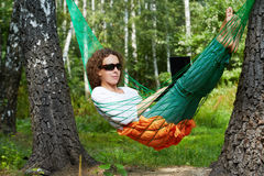 Young woman in dark sunglasses lies in hammock outdoors. And works on notebook royalty free stock photos