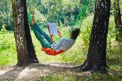 Young woman in dark sunglasses lies in hammock. Suspended between two thick birches and reads book royalty free stock image