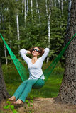 Young woman in dark sunglasses sits in hammock. Young smiling woman in dark sunglasses sits in hammock, turning his face to the sun and putting her hands behind royalty free stock photography