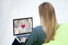 Young woman on dating website. Young beautiful single woman browsing online dating website on a laptop display. Attractive woman model sitting with notebook royalty free stock image
