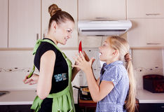 Young woman with a daughter. Young women with a daughter in the kitchen preparing Royalty Free Stock Image