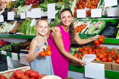 Young woman with daughter buying tomatoes Royalty Free Stock Photography