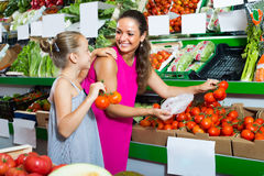 Young woman with daughter buying tomatoes Royalty Free Stock Photos