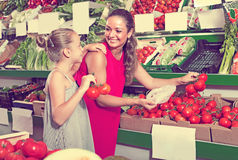 Young woman with daughter buying tomatoes Stock Photo