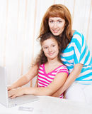 Young woman with daughter using laptop computer Royalty Free Stock Photos