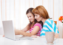 Young woman with daughter using laptop computer Stock Image