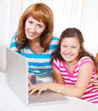 Young woman with daughter using laptop computer Stock Images