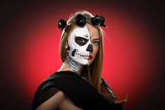 Young woman in day of the dead mask skull face art. Halloween face art on red background stock photos