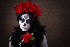 Day of the dead. Halloween. Young woman in day of the dead mask skull face art and rose. Dark background. royalty free stock image