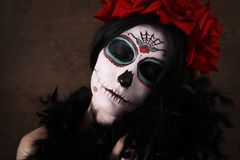 Day of the dead. Halloween. Young woman in day of the dead mask skull face art and rose. Dark background. Young woman in day of the dead mask skull face art and stock photo