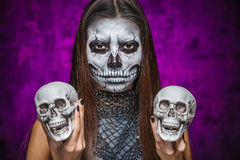 Young woman in day of the dead mask skull face art with two skul. Ls in hands. Halloween face art Royalty Free Stock Photos