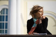 Young woman daydreaming. Young happy woman daydreaming against office wall Royalty Free Stock Photos