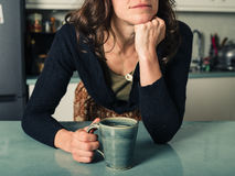 Young woman daydreaming with coffee in kitchen Royalty Free Stock Images