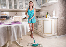 Young Woman Daydreaming and Mopping Kitchen Floor Royalty Free Stock Photo