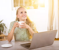 Young woman daydreaming in office. Pretty young blonde woman sitting with laptop at desk and daydreaming Royalty Free Stock Photo