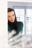 Young woman daydreaming by window Stock Photography