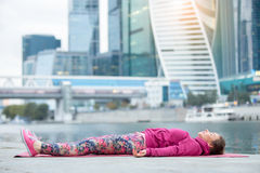 Young woman in Dead Body pose against the skyscraper Stock Photos