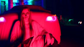 Woman with dead bride make-up for Halloween standing by the car in the white bride dress in the dark at abandoned house. The young woman with dead bride make-up stock footage