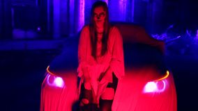 Woman with dead bride make-up for Halloween standing by the car in the white bride dress in the dark at abandoned house. The young woman with dead bride make-up stock video footage