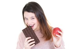 Young woman deciding between chocolate bar eating apple. A Young woman deciding between chocolate bar eating apple stock image