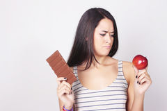 Young woman deciding between eating chocolate or apple Royalty Free Stock Image