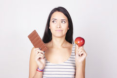 Young woman deciding between eating chocolate or apple Royalty Free Stock Photo