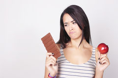 Young woman deciding between eating chocolate or apple Stock Photos