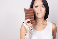 Young woman deciding holding chocolate and measure tape Royalty Free Stock Images