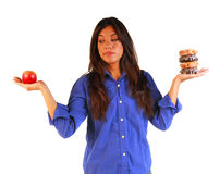 Young woman deciding to eat apple or donuts Royalty Free Stock Image