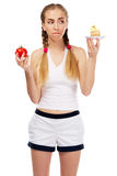 Young woman deciding on a tomato and a cake Royalty Free Stock Photos