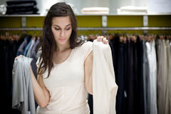 Young woman deciding which piece of clothing she Royalty Free Stock Photography