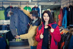 Young woman deciding on windcheater in store. Young women deciding on windcheater in sports clothes store Royalty Free Stock Image