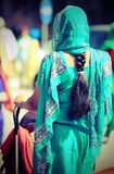 Young woman with decorated dress and long black hair braid comin. G out of the veil while pushing a stroller to the city Royalty Free Stock Image