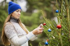 A young woman decorates the Christmas tree. With Christmas balls. Outdoor. A woman is wearing a sweater and a blue hat stock photo