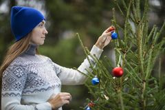 A young woman decorates the Christmas tree. With Christmas balls. Outdoor. A woman is wearing a sweater and a blue hat stock photography