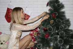 Young woman decorates christmas tree Royalty Free Stock Photography