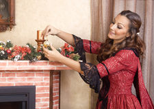 Young woman  decorates fireplace for Christmas Eve,retro style Stock Photography