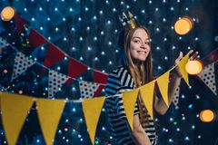 A young woman decorates room Flags, garlands preparing for the celebration Christmas. stock photos