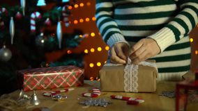 Young woman decorates a white bow with a gift box. A young woman in a striped sweater tie an openwork white bow on a box with a gift next to a Christmas tree in stock video